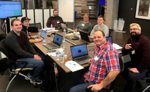 Seven teammates sit at a long table with laptops in front of them and a large monitor at the back. All of them smile at the camera.